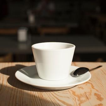 コーヒーカップと机の上のスプーンのクローズアップ