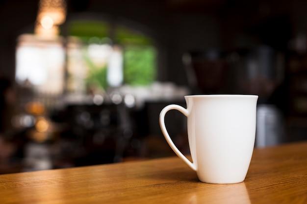 デフォーカス背景を持つ木製の机の上のコーヒーのマグカップ