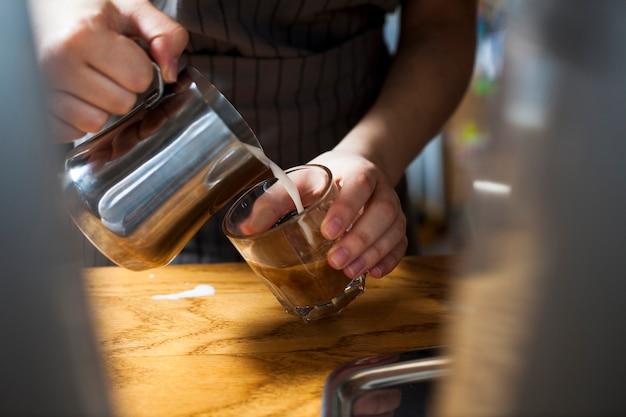 木製のテーブルの上のラテコーヒーを準備するバリスタ手のクローズアップ