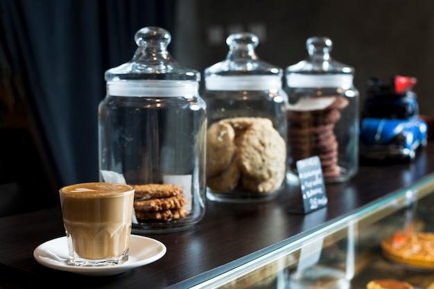 カフェのカウンターでラテコーヒーカップと様々なクッキーの瓶