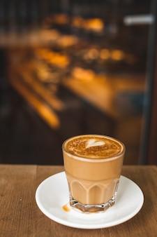 コーヒーショップで木製のテーブルの上の愛の芸術とおいしいカフェラテのガラス