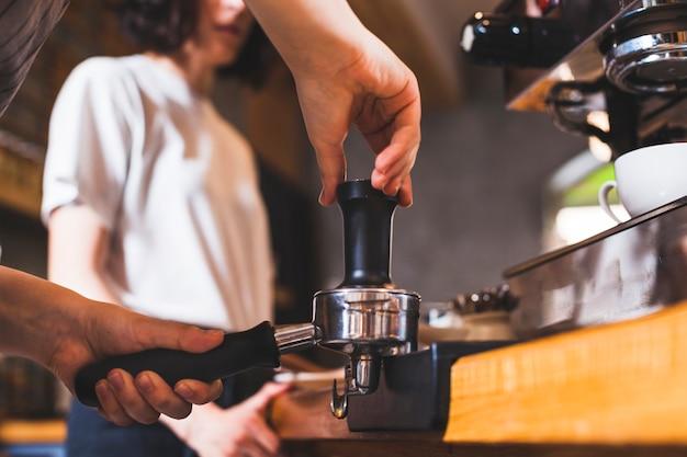 バリスタ手のコーヒーショップでカプチーノを準備