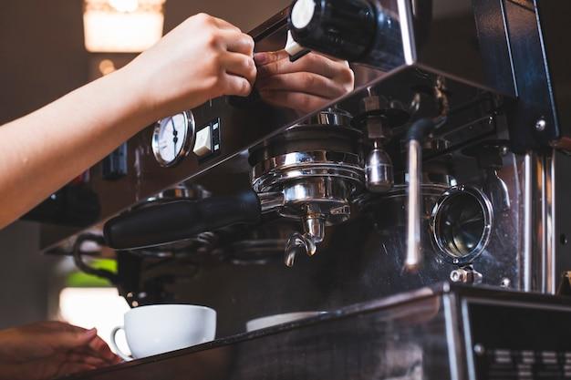 コーヒーショップでコーヒーを作る手のクローズアップ