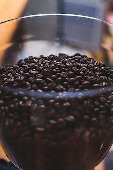 多くのコーヒー豆とガラスのボウルのクローズアップ