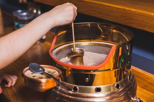 人間の手がカフェで砂の上のトルココーヒーを作る