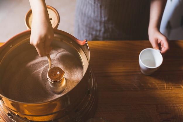 砂の中のトルココーヒーを準備する女性の手の上から見る