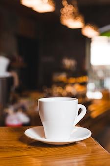 コーヒーショップの木製のテーブルの上のコーヒーカップのクローズアップ