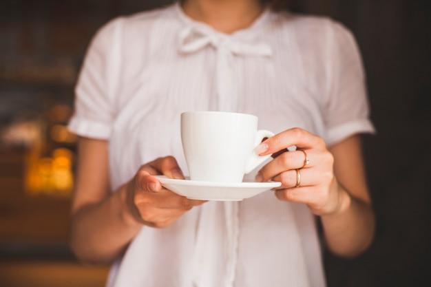 Животик женщина держит чашку кофе, стоя в ресторане