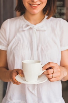 おいしいコーヒーのカップを保持している若い女性の笑みを浮かべてください。