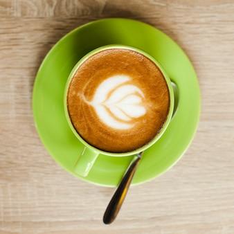 木製の表面上の美しいカフェラテアートと緑のコーヒーカップのトップビュー