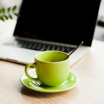 グリーンコーヒーカップと木製の机の上のノートパソコンを開く