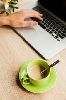 木製の机の上のコーヒーのカップとラップトップを使用している人の手