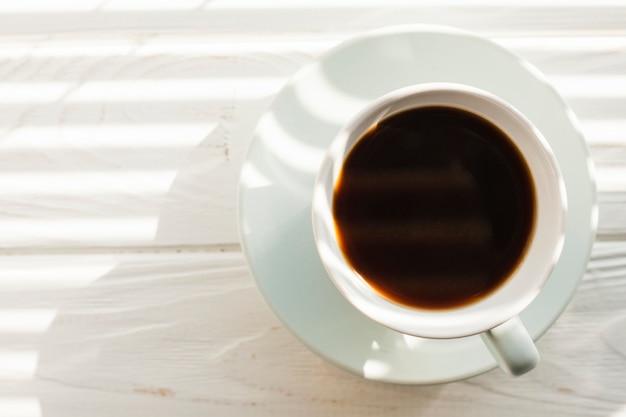 白い木製のテーブルの上のおいしいコーヒーカップの立面図