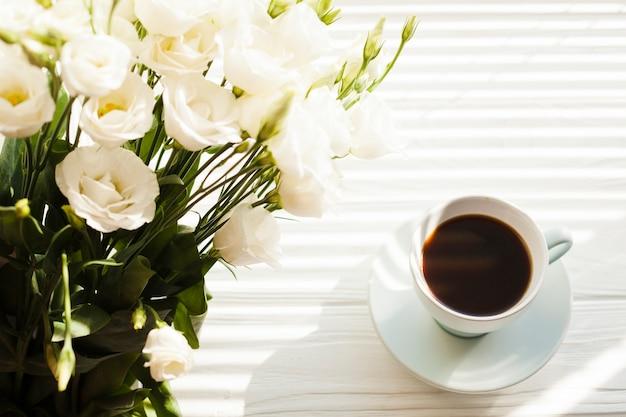 机の上のブラックコーヒーカップと白いバラの花束