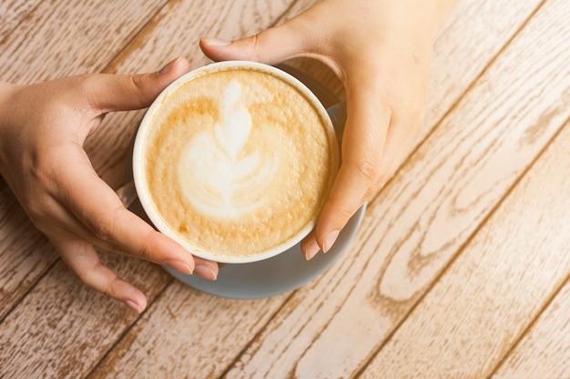 木製の表面にラテコーヒーカップをかざす人間の手の上から見る