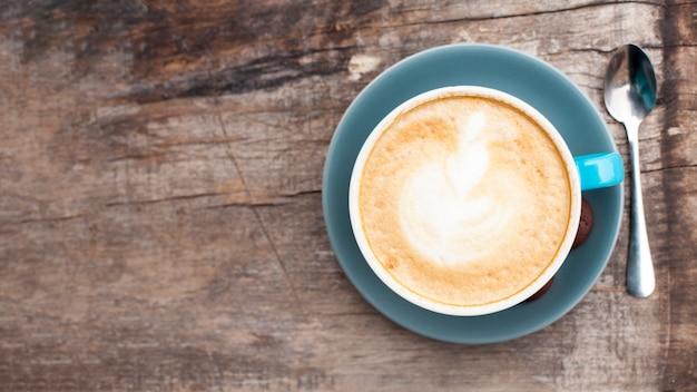 古い木製の背景に泡立った泡とおいしいコーヒーの高角度のビュー