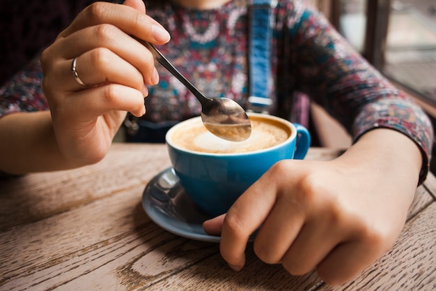 レストランで熱い一杯のコーヒーを保持している女性