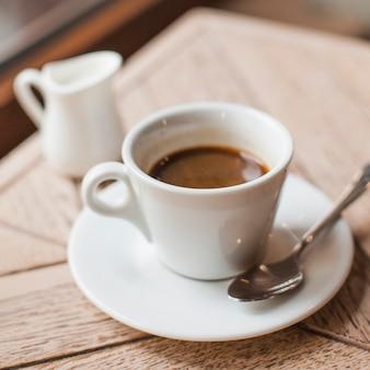 カフェの木製のテーブルの上のコーヒーカップのクローズアップ