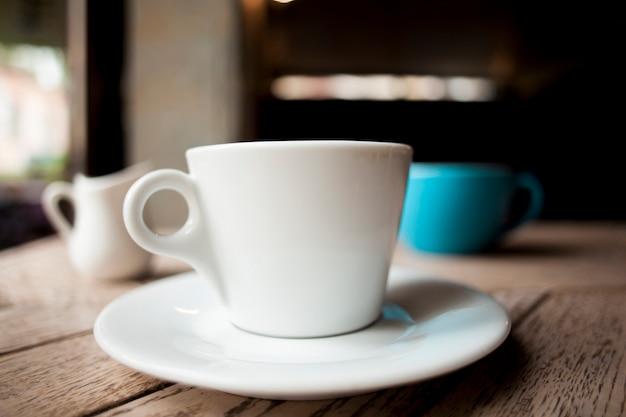 伝統的な白いコーヒーカップ、木製のテーブル