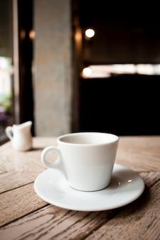 木製のテーブルの上の受け皿と白いセラミックコーヒーカップ
