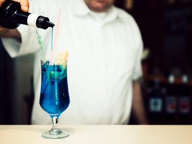 Бармен наполняет бокал синим алкогольным напитком