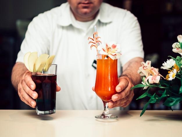 アルコールカクテルを出すバーテンダー