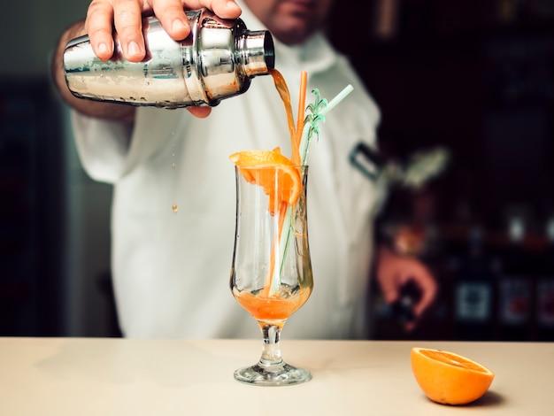 Мужской бармен наливает коктейль из шейкера