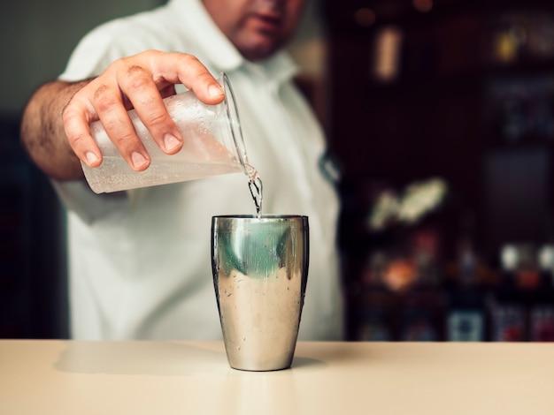 Мужской бармен, смешивая коктейль в шейкере