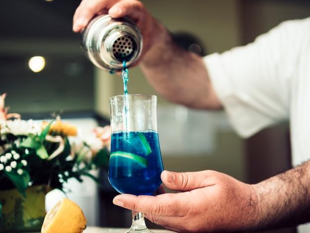バーテンダーのカクテルでアルコール飲料を注ぐ