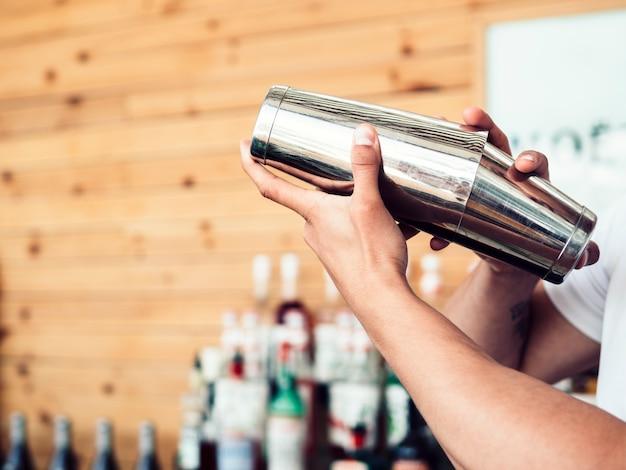 Бармен готовит коктейль в шейкере