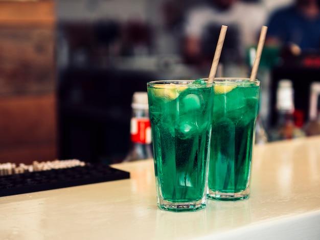 Декорированные бокалы из разноцветного зеленого напитка