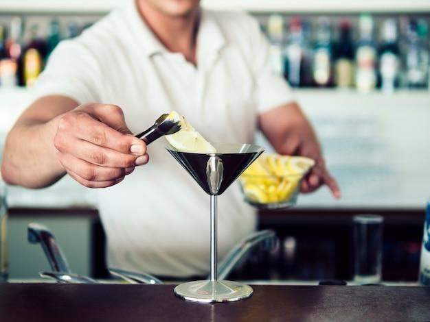 ステンレスマティーニグラスでカクテルを提供する男性のバーテンダー