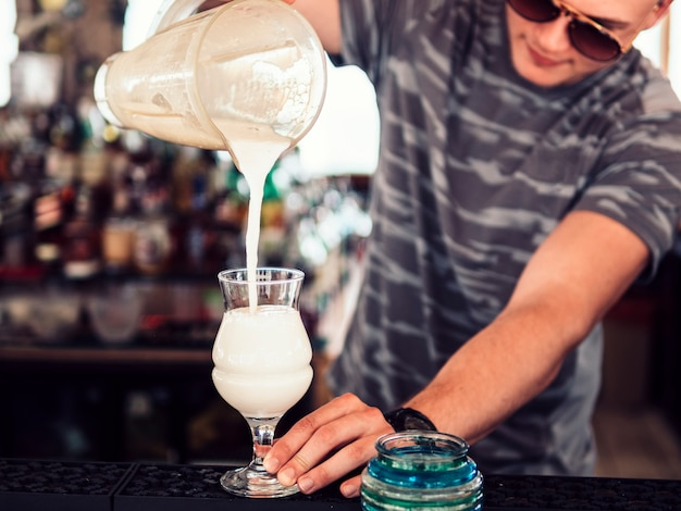 ガラスのバーマン注ぐミルクセーキ