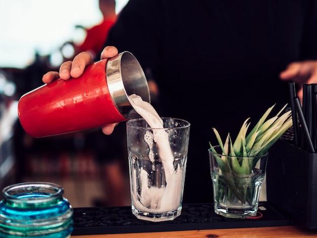 Безликий бармен, наполняя стакан молочным коктейлем в баре