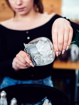 Женский бармен готовит напиток со льдом
