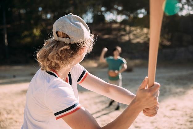 若い女性が野球のバットで打つ準備ができて