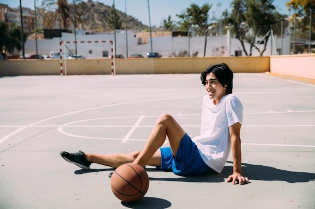 バスケットボールピッチで座っている陽気な十代の少年