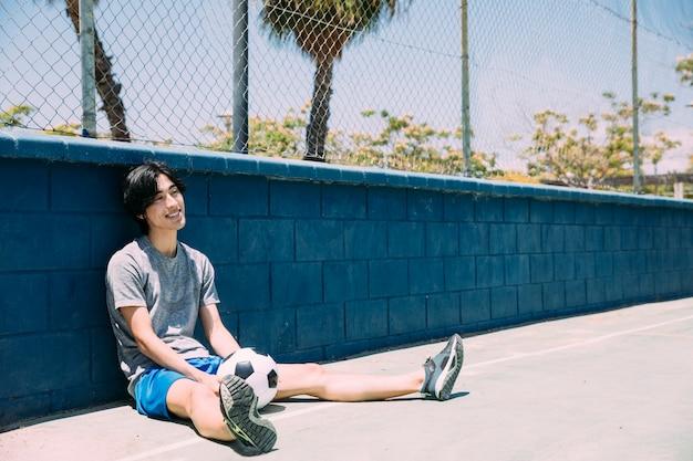 サッカーとフェンスに座っている若い男の笑みを浮かべてください。