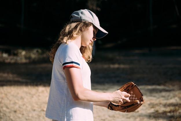 Молодая женщина готовится к бейсбольному полю