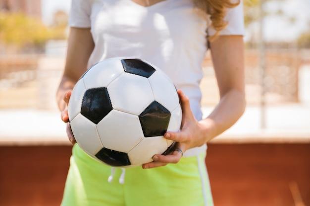 Молодая женщина, стоя с футбольным мячом
