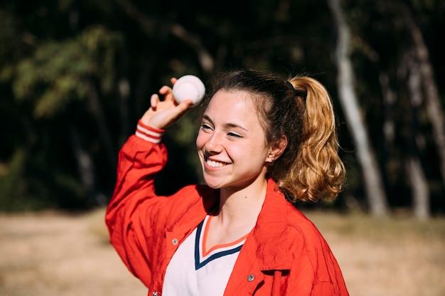 Веселый подросток студент бросает бейсбол