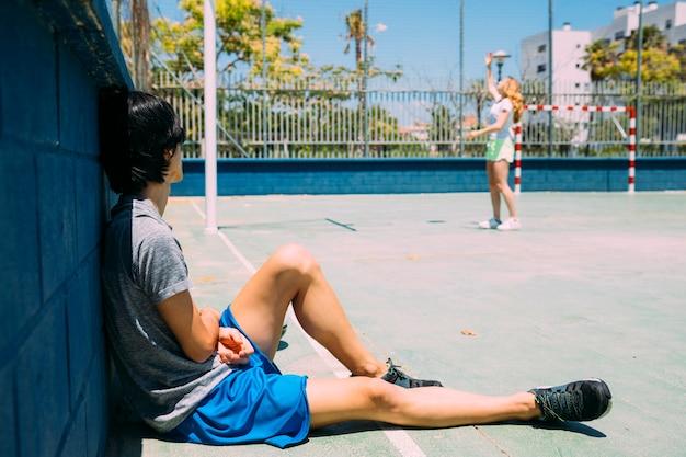 トレーニングの後休んでいるアジアの若い男