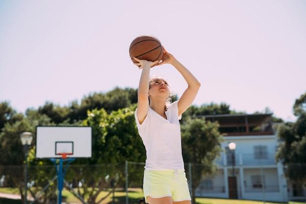 Активный подросток играет в баскетбол на корте