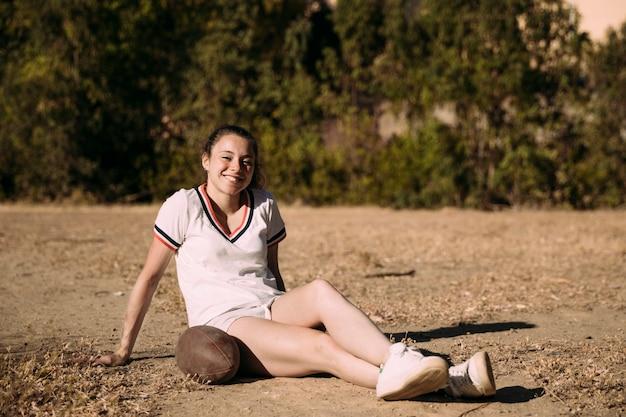 Игривая молодая женщина, сидящая с мячом для регби
