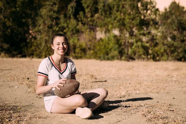 ラグビーボールと座っている陽気なティーンエイジャー