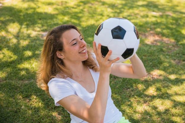 サッカーと草の上に座っている若い女性の笑みを浮かべてください。