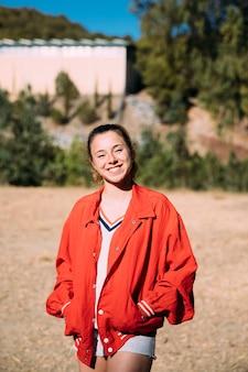 カメラを見て赤いジャケットの若い女性