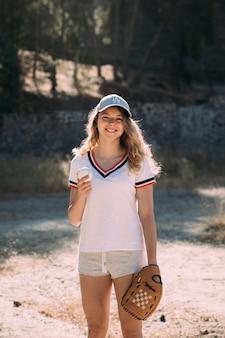 野球とグローブを屋外でアクティブな女性の笑みを浮かべてください。