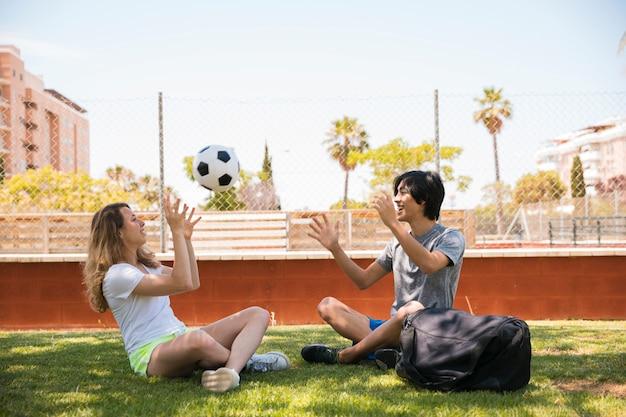 多民族のカップルが草の上に座っている間サッカーボールを投げる