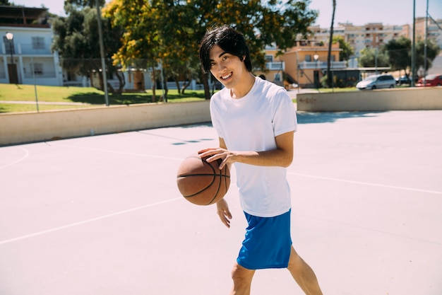 Улыбающийся азиатский подросток студент играет в баскетбол